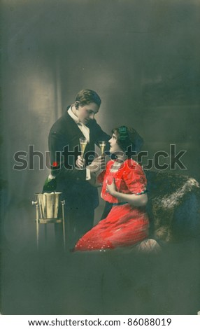 RUSSIA - CIRCA 1915: Retro postcard depicts loving couple with wine glasses, circa 1915, Russia. Vintage hand-tinted photograph - stock photo