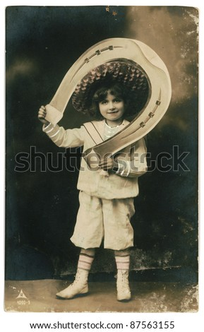 RUSSIA - CIRCA 1906: Retro postcard with weathered edges on white background printed in circa 1906, Russia. Vintage hand-tinted photograph depicts a young boy with big horseshoe - stock photo