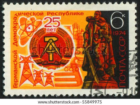 RUSSIA - CIRCA 1974: stamp printed by Russia, shows Arms of DDR and Soviet War memorial, Treptow, circa 1974.