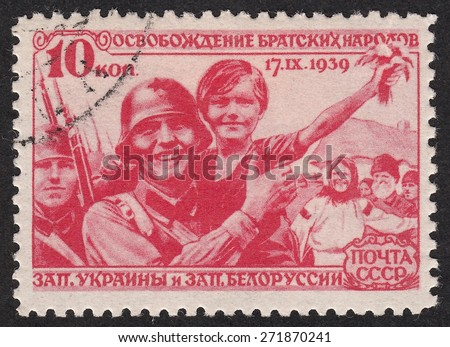RUSSIA - CIRCA 1940: stamp printed by Russia, shows Soviet soldier with a child.The liberation of the fraternal peoples of Western Ukraine and Western Belorussia, circa 1940 - stock photo