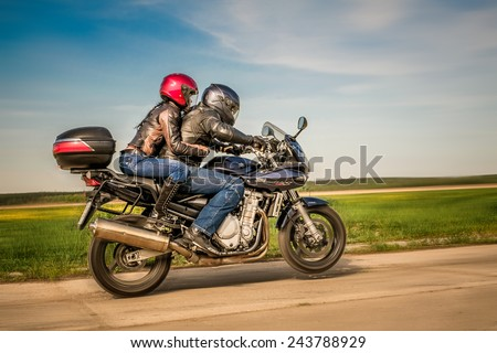 RUSSIA-JULY 7, 2013: Man and woman on a Suzuki Bandit bike doing wheelies. Suzuki Bandit is a series of sport-standard motorcycles. Suzuki Motor Corporation is a Japanese multinational corporation. - stock photo