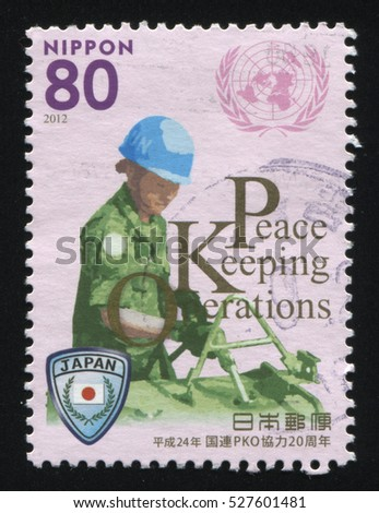 RUSSIA KALININGRAD, 22 APRIL 2016: stamp printed by Japan, shows woman in military unoform loading tank, circa 2012
