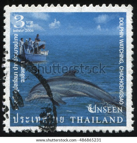 RUSSIA KALININGRAD, 3 JUNE 2016: stamp printed by Thailand, shows dolphin and a boat in the sea, circa 2004