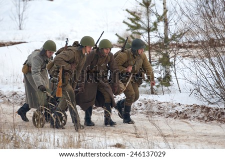 RUSSIA, LIZLOVO - DECEMBER 14: Unidentified soldiers transport the machine gun Maxim on reenactment of the counterattack under the Moscow in 1941 in World War II  Lizlovo village, Russia, 2014