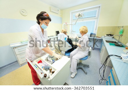 RUSSIA, MOSCOW - AUG 31, 2015: Dentist and her assistant preparing for oral examination of patient, young male patient sitting in chair in dental office of Center Endosurgery and Lithotripsy (CELT)