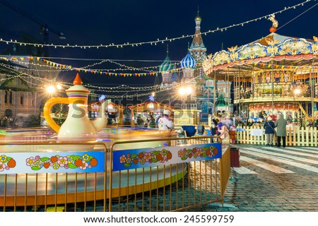 Russia, Moscow - 15 January, 2015: People shopping, ride a carousel and walking at New Year's  market on the Red Square on January 15, 2015, Moscow, Russia. - stock photo