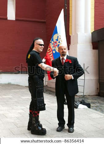 RUSSIA, MOSCOW - JULY 19: Goth and a man in a costume of Lenin shaking hands on Red Square in Moscow on July 19, 2008. Red Square is famous for the resting place of Lenin - Lenin's Mausoleum