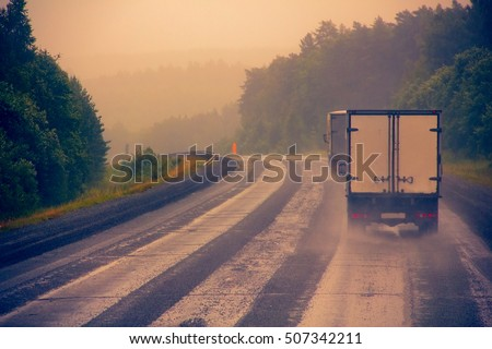 Russia, Novosibirsk - July 27, 2016: lorry on highway-delivery of goods in bad weather threat. traffic on wet bad highway. - Be careful on turns and during overtaking!