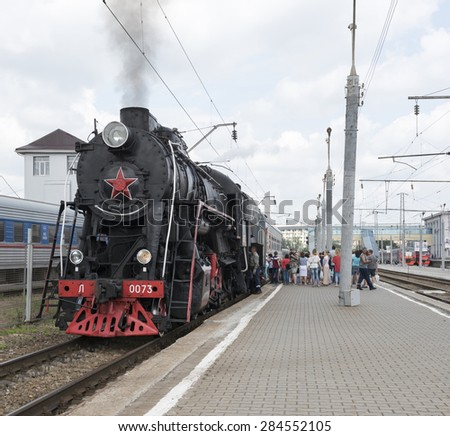 RUSSIA; ROSTOV-ON-DON - MAY 31 - Passengers sit in a car, driven by a steam locomotive. Mechanics lubricated steam locomotive on May 31,2015 in Rostov-on-Don