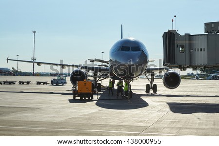 Russia, Saint-Petersburg, 14 June 2016: The big plane has approached a sleeve of unloading of passengers at the Pulkovo airport and the service of maintenance has begun work, a sunny day, a silhouette