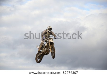 "RUSSIA, SAMARA, CHAPAYEVSK - OCTOBER 17: Spectacular jump motocross racer A.Ivanyutin on the background a stormy sky the Open Cup ""Volga"" motocross on October 17, 2011 in Chapayevsk, Samara, Russia"