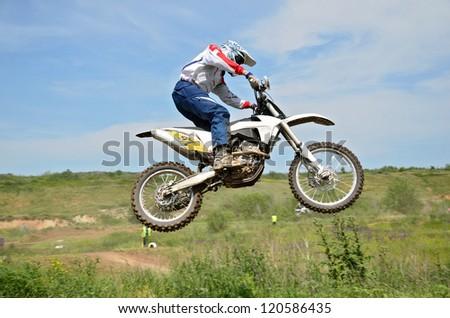 RUSSIA, SAMARA - JUNE 16: Rider motorcycle V. Sorokin performs a jump in background of blue sky, the Regional Motocross Championship on June 16, 2012 in Samara, Russia - stock photo
