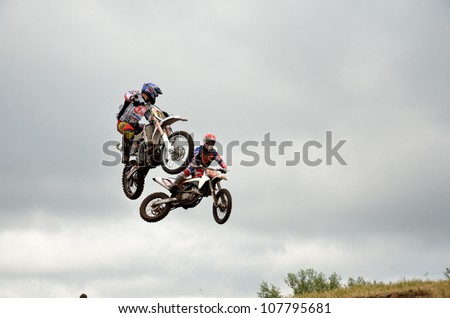 RUSSIA, SAMARA - JUNE 16: Two motorbike racers 666 A. Nikishkin and 19 M. Kozlov the competition on in flight the Regional Motocross Championship on June 16, 2012 in Samara, Russia - stock photo