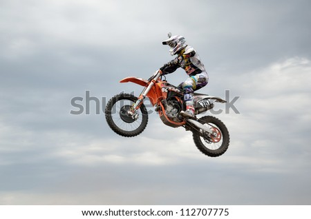 RUSSIA, SAMARA - MAY 6: MX racer D. Vintaev performs a jump in background of clouds, the Open class the Regional Motocross Championship on May 6, 2012 in Samara, Russia - stock photo