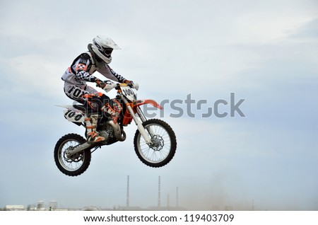 RUSSIA, SAMARA - MAY 6: Young MX rider E. Pershin on a motorcycle in the air, on the background of the cloudy sky  the 85 sm3 class the Regional Motocross  on May 6, 2012 in Samara, Russia - stock photo