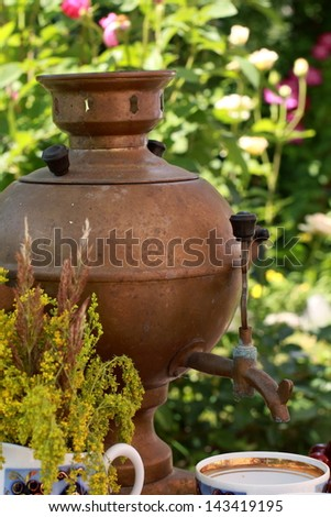 Russian Antiques/Antique samovar and ceramic tea service in the summer garden - stock photo