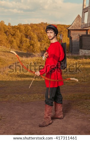 Russian archer with the wooden bow in traditional red suit and fur hat. Summer forest on the background. - stock photo