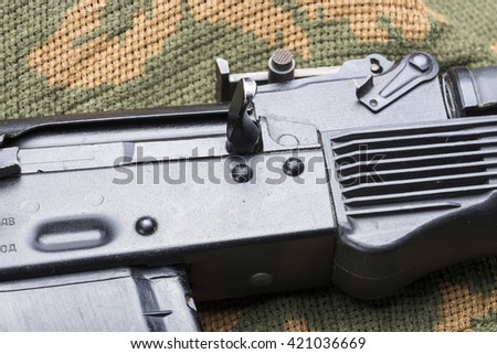 Russian assault rifle AK-47 on camouflage clothing - stock photo