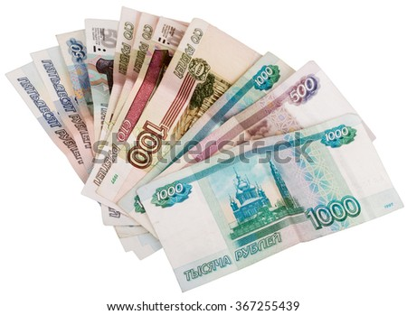Russian banknotes lie on a table fan. Different nominal money is not new on the table isolated on white background.