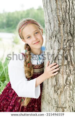 Russian beautiful girl in ethnic costume at tree - stock photo