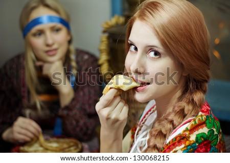 Russian beautiful girl in national costume eating pancake - stock photo