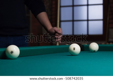 Russian billiard balls on green game table cloth and player