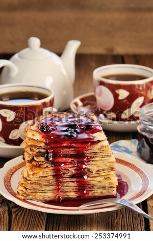 Russian bliny with currant jam, tea cups, pot on wooden background closeup - stock photo