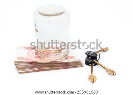 Russian cash banknotes under glass bottle with house key near, white background - stock photo