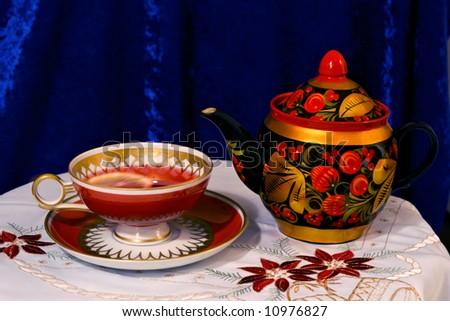 "russian ceramic tea pot painted in ""hohloma"" style and a cup of red tea with a slice of lemon on a white table cloth with xmas floral pattern - stock photo"