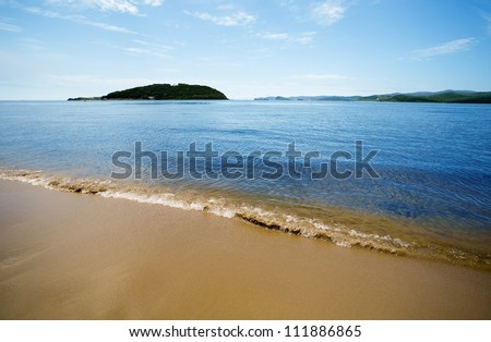 Russian coast of the Sea of Japan. Primorsky Kray. In the background a vessel. - stock photo
