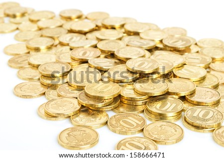 Russian coins from the yellow metal scattered on a white plane.
