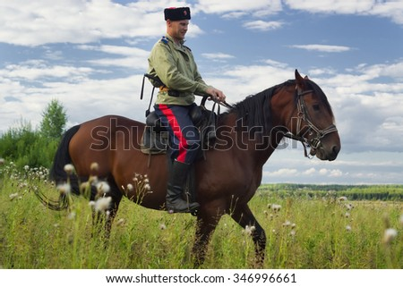 Russian Cossack uniformed WWI inspecting the border on horseback  - stock photo