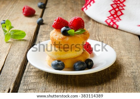 Russian cottage cheese pancakes with raspberries on wooden background. Selective focus.