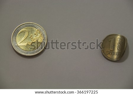 Russian economic crisis concept. Two euro coin and crumpled one rouble coin. - stock photo
