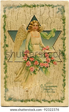 RUSSIAN EMPIRE - CIRCA 1929: Reproduction of antique postcard shows angel holding a wreath of roses, circa 1929 Text in Russian - Happy Christmas - stock photo