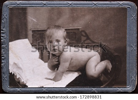 RUSSIAN EMPIRE - CIRCA 1910s: An antique photo shows studio portrait of a little boy on his stomach on a piece of white fabric in an armchair