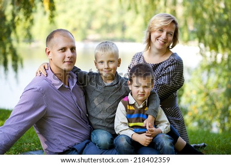 Russian family, young parents and two sons in autumn park
