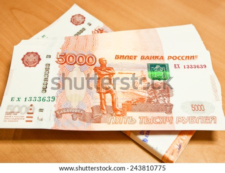 Russian five thousand rubles banknotes on the table. - stock photo