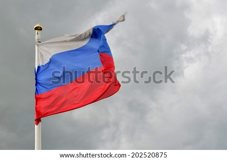Russian flag fluttering with the dark grey sky at the background - stock photo