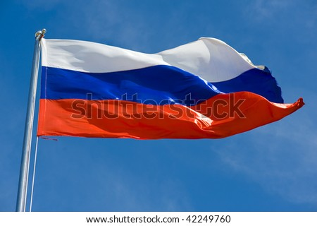 russian flag on a pole against blue sky - stock photo