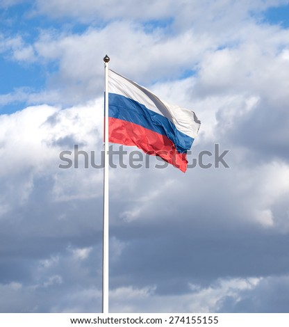 Russian flag on flagpole waving on a clear sunny day on a blue sky with many rainy clouds. Vertical photo