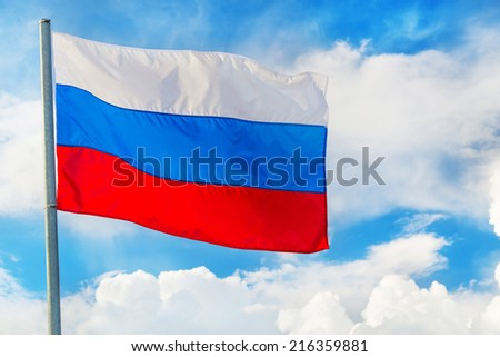 Russian flag waving in the wind over blue sky with white clouds - stock photo