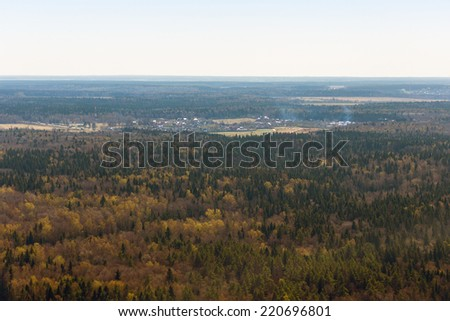 Russian forest during fall and a small settlement in the background. View from the helicopter. - stock photo