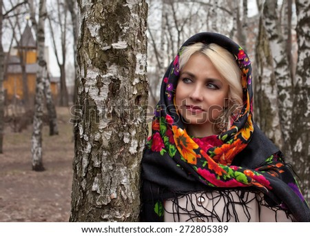 Russian girl in a headscarf is worth about birch - stock photo