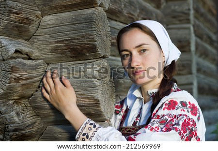 Russian girl in ethnic costume at russian log hut - stock photo