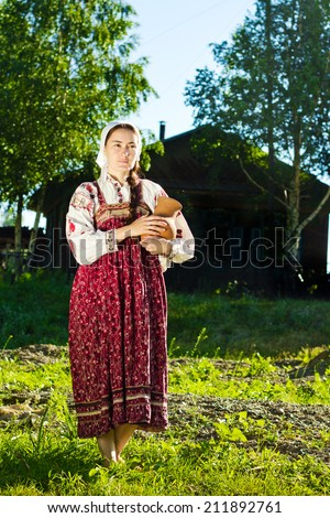 Russian girl in ethnic costume in village with jug - stock photo