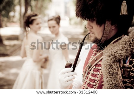 Russian hussar in vintage outfit is smoking his pipe. Two pretty women on the background are looking at him.  Retro-styled photo.