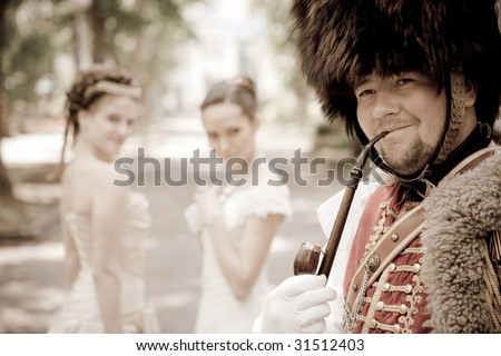Russian hussar in vintage outfit is smoking his pipe. Two pretty women on the background are looking at him. - stock photo