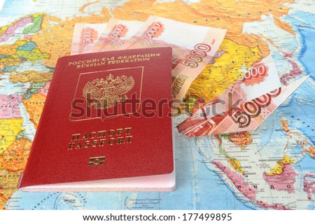 Russian international passport with money within and origami plane made from money on the world map - stock photo