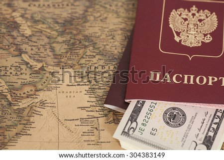 Russian International passports with dollars on the world map - stock photo